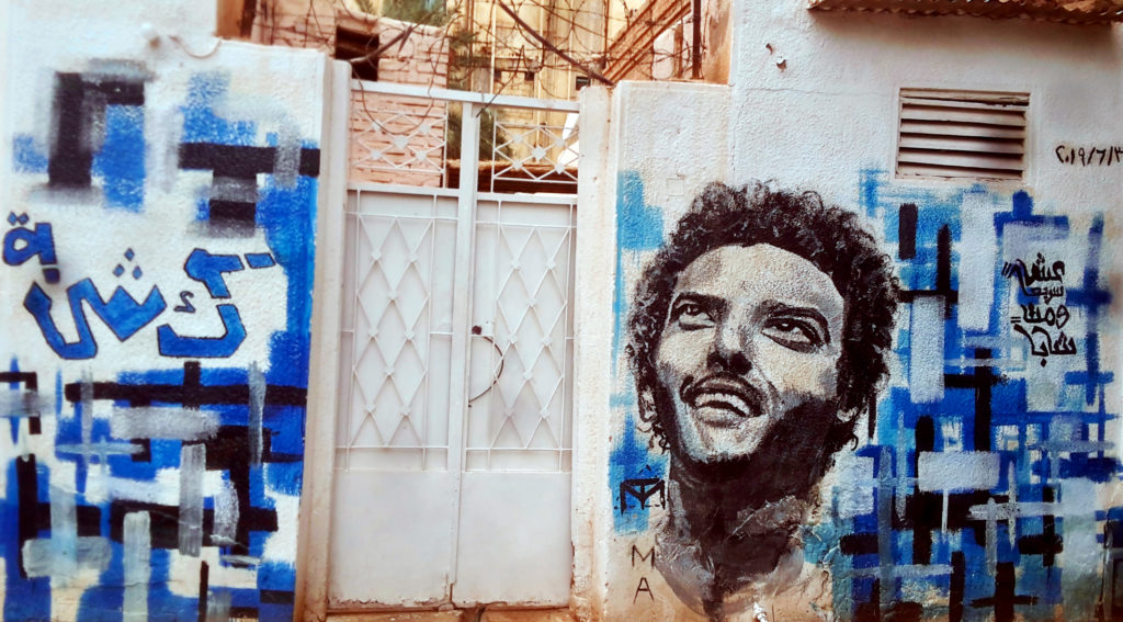 """A mural on Abdelsalam Kisha's house depicting him and his famous saying: """"Live fast and die young""""."""